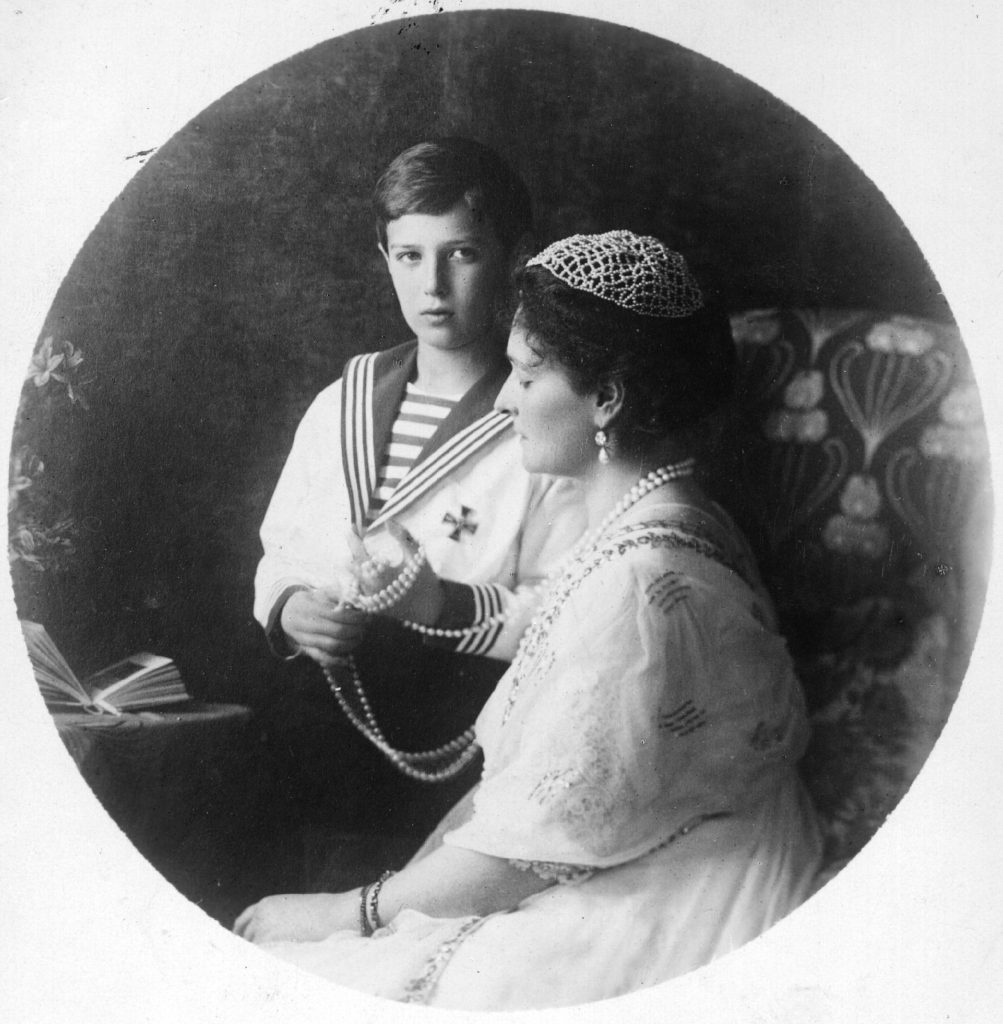 1915: Tsarina Alexandra Feodorovna, wife of Tsar Nicholas II, and her son the Tsarovitch who is playing with her pearls.